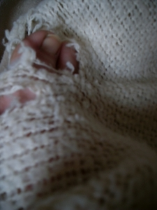 Who takes pictures of their own toes in a past-its-prime blanket?